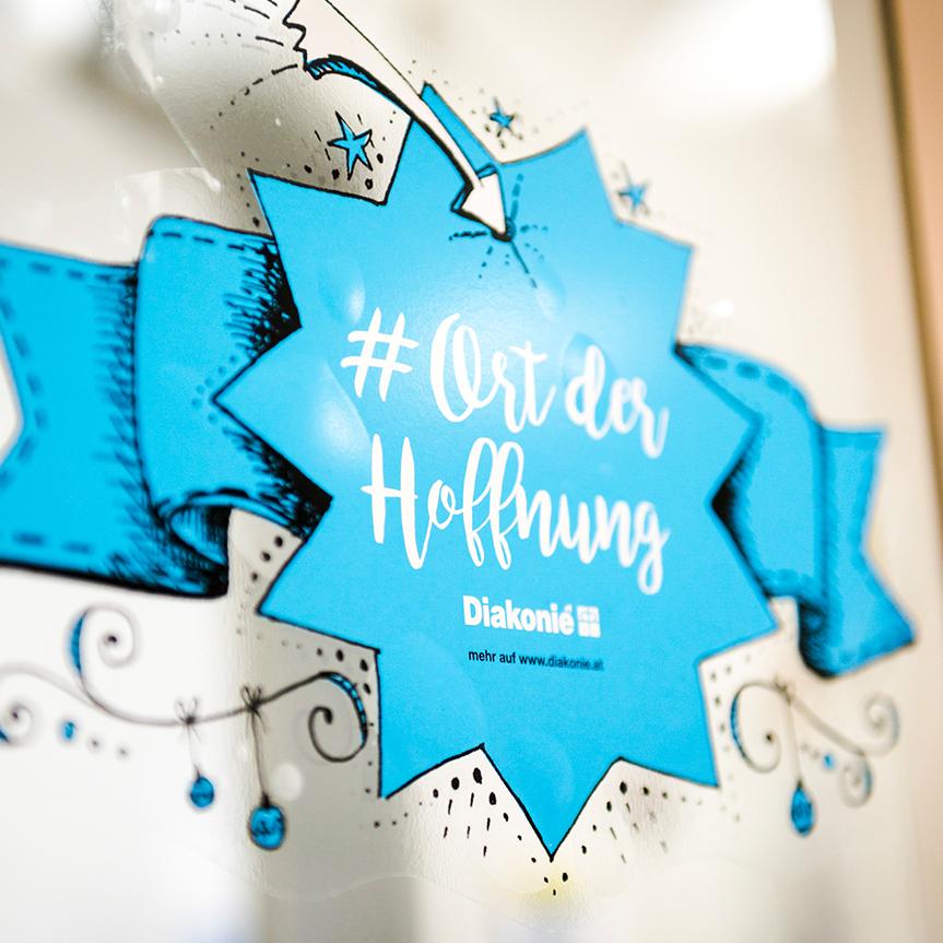 """Auf einer Tür klebt ein blauer Sticker in Sternform. Darauf steht """"#Ort der Hoffnung"""" und das Logo der Diakonie"""