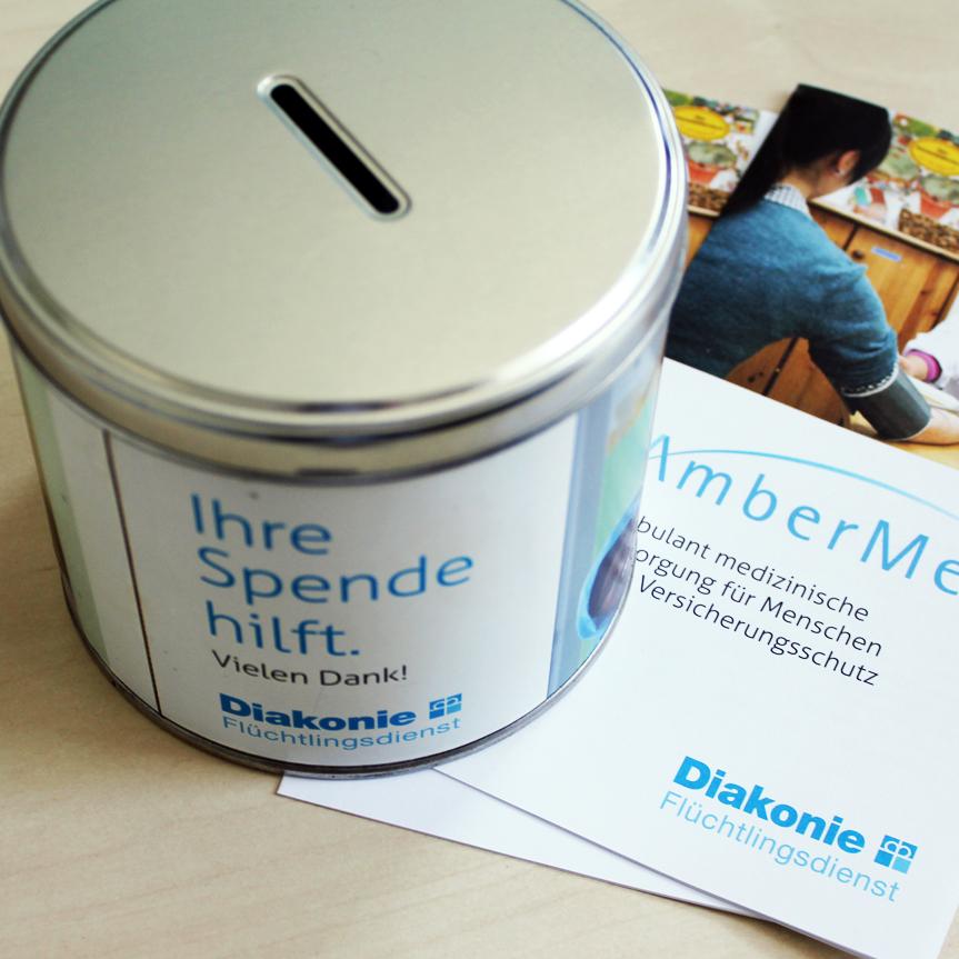 Foto einer Spendendose, die auf einem AmberMed Folder steht.
