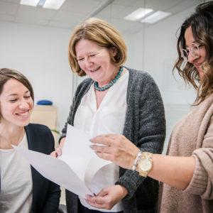 Drei Frauen vom hauptamtlichen Team von AmberMed betrachten Unterlagen