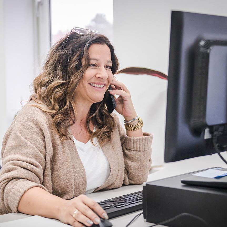 Eine Frau sitzt am Schreibtisch vor dem Computer und telefoniert
