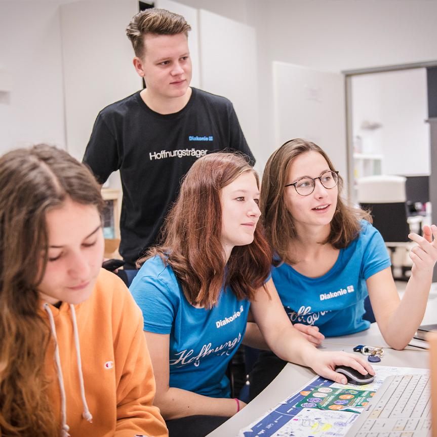 Eine Gruppe von Freiwilligen sitzt vor einem Computer