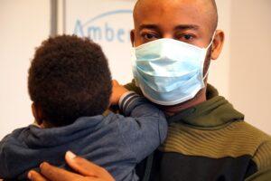 Ein Mann trägt einen Mund-Nasen-Schutz und hält sein Kind